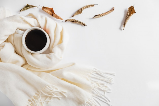 Autumn composition. cup of coffee, scarf and dried leaves on gray background. flat lay, top view, copy space