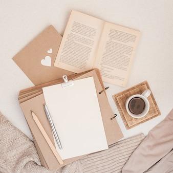 秋の組成。コーヒー、本、毛布、ノート、女性のファッションセーターのカップ。
