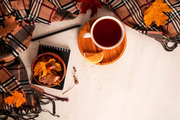 Autumn composition. a cup of tea, scarf, autumn leaves, glasses, notepad, pencil. flat lay, top view, copy space. high quality photo