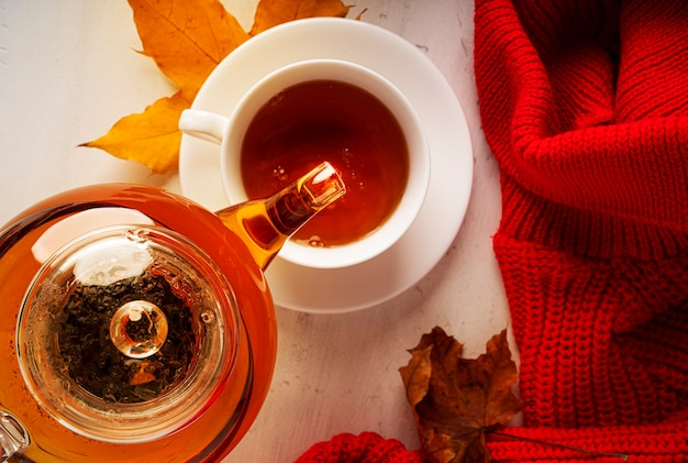 Autumn composition. a cup of tea and teapot, red sweater, autumn leaves. flat lay, top view, copy space. high quality photo