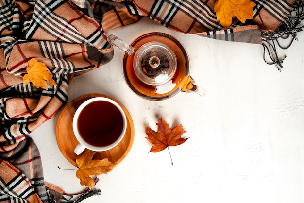 Autumn composition. a cup of tea and teapot, scarf, autumn leaves. flat lay, top view, copy space. high quality photo
