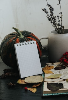 Autumn composition on a dark background, cozy atmosphere, tea, books, foliage