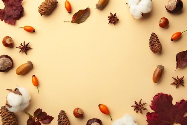 秋の構成。ベージュの背景に乾燥した葉、花、ベリー。感謝祭の日のコンセプト。フラットレイ、上面図、コピースペース