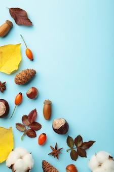 秋の構成。青の背景に乾燥した葉、花、ベリー。感謝祭の日のコンセプト。フラットレイ、上面図、コピースペース
