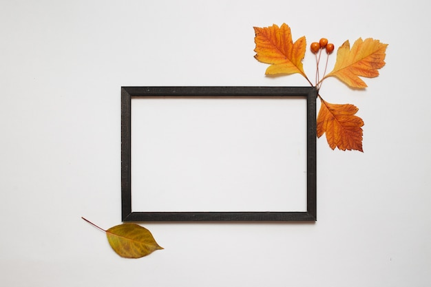 Autumn composition, flat lay. wooden photo frame with fresh autumn leaves on white background