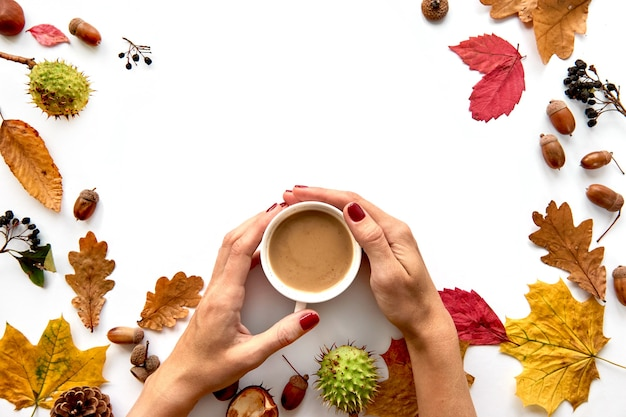 Autumn composition. frame made of dried leaves, branches, pine cones, berries, acorns and hand with cup of coffee on white background. template mockup fall, halloween. flat lay, copy space background.
