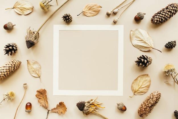 秋の構成。パステルカラーの背景にどんぐり、コーン、乾燥した葉、乾燥した花で作られたフレーム。秋、秋のコンセプト。フラットレイ、上面図、コピースペース。