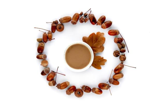 가 구성입니다. 갈색 말린 잎, 도토리, 흰색 배경에 분리된 커피 한 잔으로 만든 프레임입니다. 템플릿 모형 가을, 할로윈, 추수 감사절 개념. 평면 위치, 상위 뷰 배경