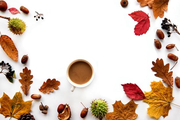가 구성입니다. 말린 잎, 나뭇가지, 솔방울, 딸기, 도토리, 손으로 만든 프레임에는 흰색 바탕에 커피 한 잔이 있습니다. 템플릿 모형 가을, 할로윈. 평평한 위치, 복사 공간 배경.