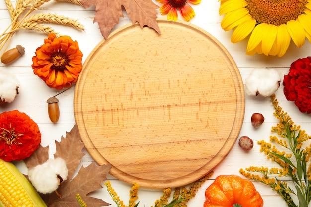 Осенняя композиция. рама из свежих цветов на белом фоне деревянных. плоская планировка, вид сверху, копия пространства. день благодарения