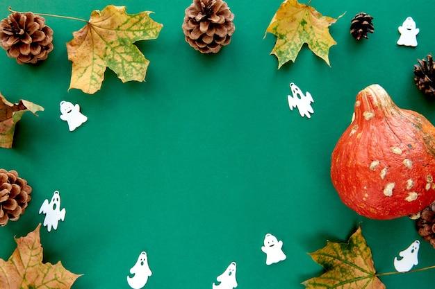 秋の構成。カボチャ、乾燥した葉、装飾的なゴーストの背景で作られたフレーム。テンプレート秋、秋、ハロウィーン、収穫感謝祭のコンセプト。フラットレイ、上面図、コピースペースの背景