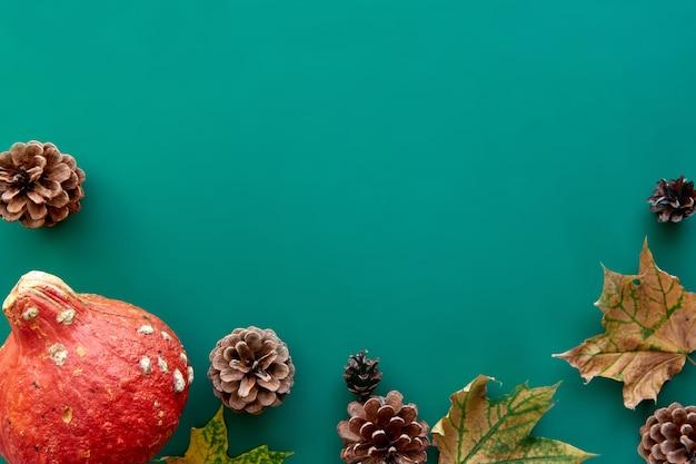 秋の構成。カボチャ、乾燥した葉と松ぼっくりの背景で作られたフレーム。テンプレート秋、秋、ハロウィーン、収穫感謝祭のコンセプト。フラットレイ、上面図、コピースペースの背景