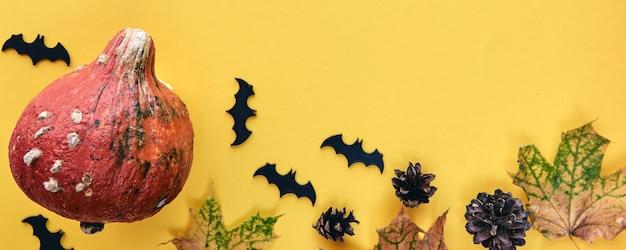 秋の構成。カボチャ、乾燥した葉、松ぼっくり、背景で作られたフレーム。テンプレート秋、秋、ハロウィーン、収穫感謝祭のコンセプト。フラットレイ、上面図、コピースペースバナー