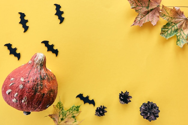 秋の構成。カボチャ、乾燥した葉、松ぼっくり、コウモリの背景で作られたフレーム。テンプレート秋、秋、ハロウィーン、収穫感謝祭のコンセプト。フラットレイ、上面図、コピースペースバナー