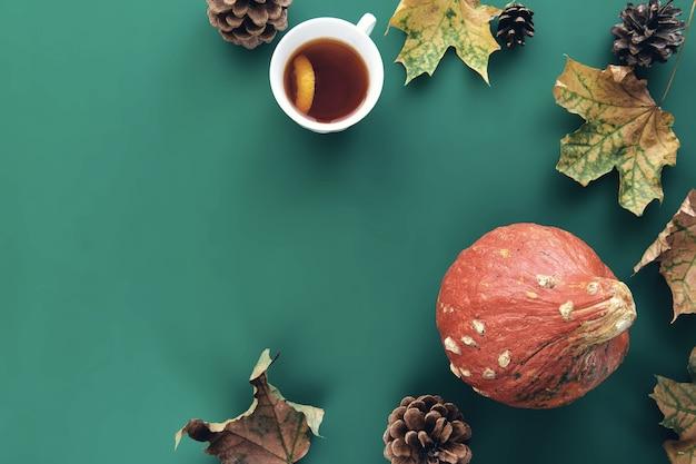 秋の構成。カボチャ、乾燥した葉、松ぼっくり、テスカップの背景で作られたフレーム。テンプレート秋、秋、ハロウィーン、収穫感謝祭のコンセプト。フラットレイ、上面図、コピースペースの背景
