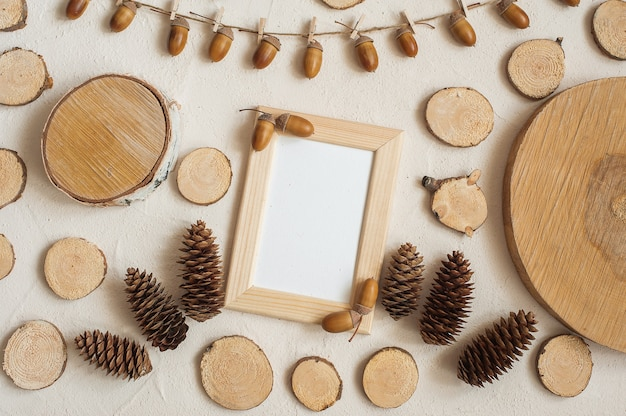 Autumn composition, frame made of pine cones, acorns and small wooden stumps.