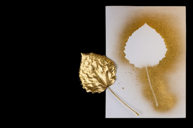 Autumn composition of gold leaf and postcards on black background