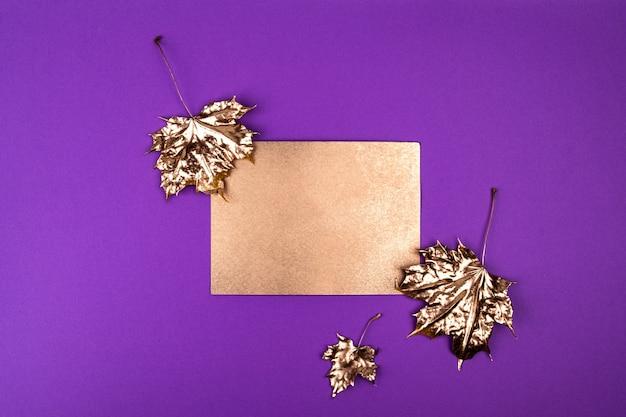 Autumn composition. golden maple leaves on purple.