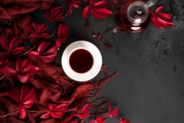 Осенняя композиция. чай каркаде в чайнике, белая чашка с блюдцем, шарф и осенние красные виноградные листья. плоская планировка. вид сверху. фото высокого качества