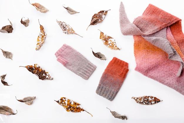 秋の構成。ニットのスカーフとミトン、白い背景に紅葉。フラットレイ、上面図。居心地の良い家のコンセプト