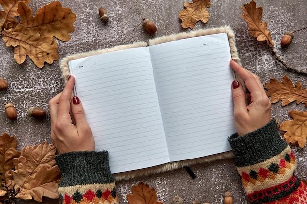 갈색 마른 잎과 도토리로 만든 가을 구성은 어두운 콘크리트 배경에 있습니다. 템플릿 모형 빈 노트북과 펜으로 손. 가을, 할로윈. 평평한 위치, 복사 공간 배경.