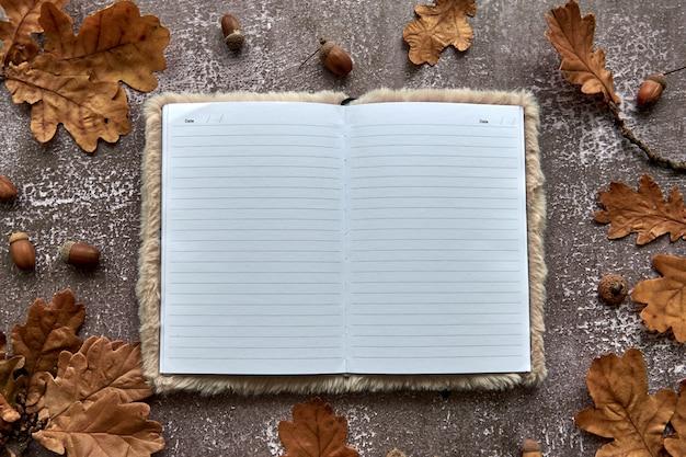 갈색 마른 잎과 도토리로 만든 가을 구성은 어두운 콘크리트 배경에 있습니다. 템플릿 모형 빈 종이 노트북. 가을, 할로윈. 평평한 위치, 복사 공간 배경.