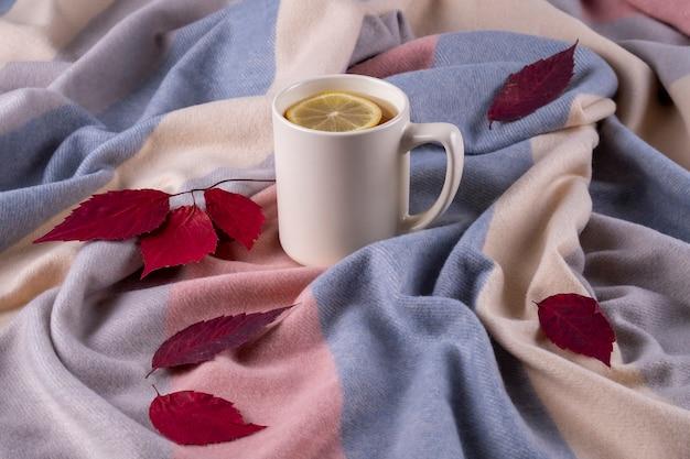 パステルカラーの柔らかく暖かいスカーフ、乾燥した紅葉、レモン入りの熱いお茶を入れたセラミックマグの秋の構成。セレクティブフォーカス。
