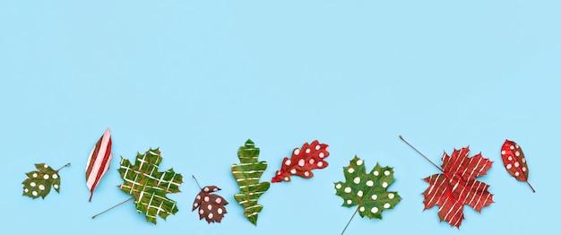 Осенняя композиция из листьев клена с дубом, окрашенная в белую полоску и в горошек