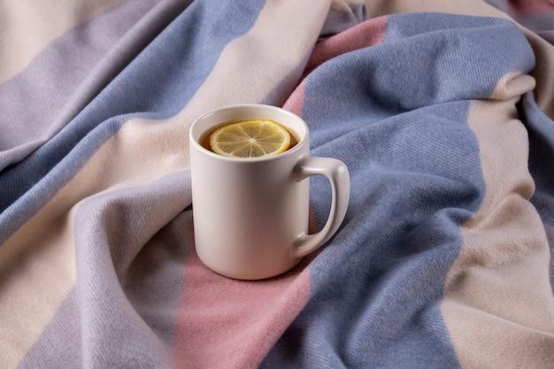パステルカラーの柔らかく暖かいスカーフとレモン入りの熱いお茶を入れたセラミックマグの秋の構成。セレクティブフォーカス。
