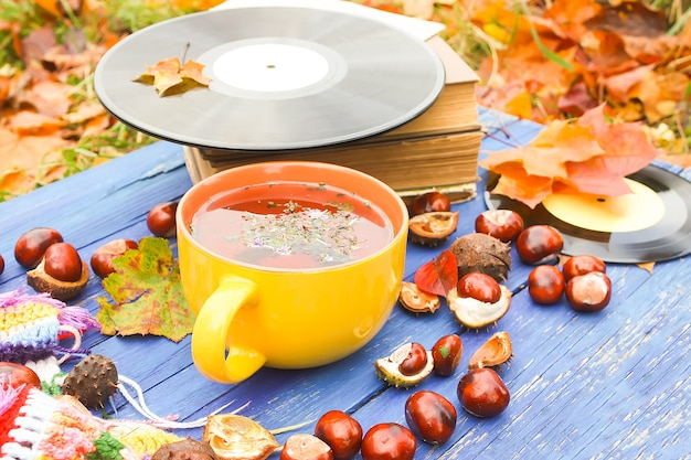 明るい手作りのかぎ針編みの格子縞、古い本、秋の紅葉と栗と古い木製の背景にハーブティーとヴィンテージビニールレコードの黄色いセラミックカップの秋の構成。