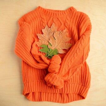 Осенняя композиция. оранжевый свитер и осенние листья на деревянных фоне