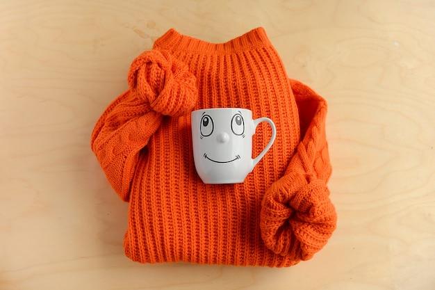 Осенняя композиция. оранжевый свитер и кружка с улыбкой на деревянном фоне