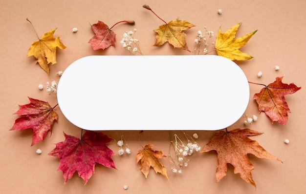 秋の構成。紙の空白、乾燥した花と茶色の背景の葉。秋、秋のコンセプト。フラットレイ、上面図、コピースペース