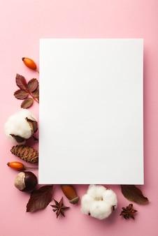 가 구성입니다. 분홍색 배경에 말린 꽃과 잎이 있는 빈 종이. 가을, 가을 컨셉입니다. 평평한 평지, 평면도, 복사 공간, 정사각형. 세로 사진