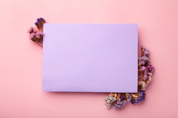 가 구성입니다. 보라색 배경에 말린 꽃과 잎이 있는 빈 종이. 가을, 가을 컨셉입니다. 평평한 평지, 평면도, 복사 공간, 정사각형