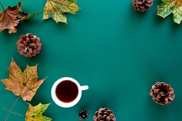 秋の構成。 10月の乾燥した葉、松ぼっくり、茶碗の背景で作られたパターン。テンプレート秋、秋、ハロウィーン、収穫感謝祭のコンセプト。フラットレイ、上面図、コピースペースの背景