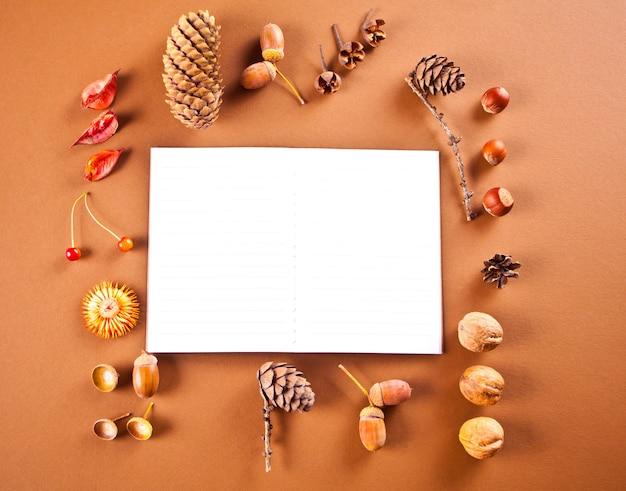 맑은 공책, 마른 잎, 원뿔, 도토리, 딸기, 견과류가 있는 가을 구성 패턴입니다.