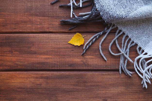 Осенняя композиция плед и желтый осенний лист на деревянном фоне с копией пространства вид сверху