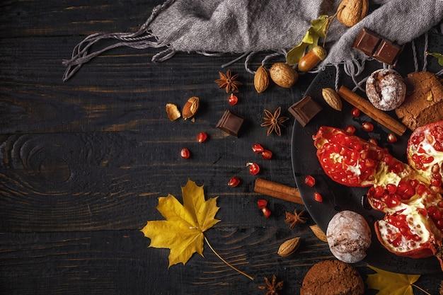 秋の組成物。ナッツ、スパイス、暗い木製のテーブルに乾燥した葉とザクロ。上面図。