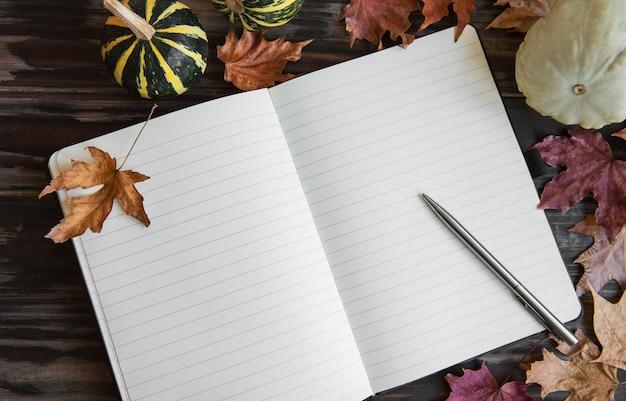 가을 구성 호박과 나무 배경에 노트북과 나뭇잎 프레임