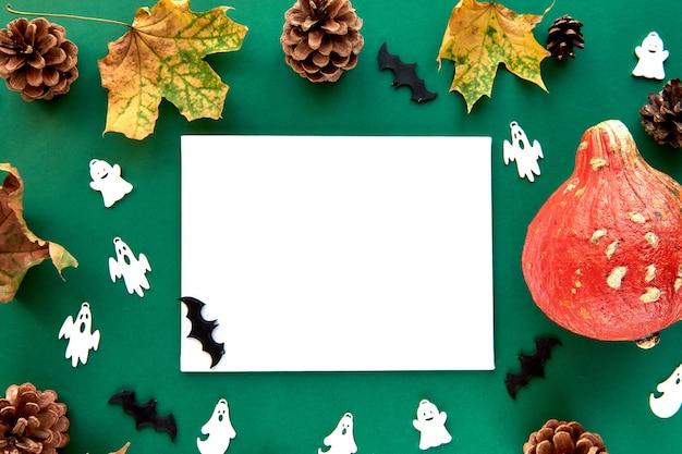秋の構成。カボチャ、乾燥した葉と装飾的なゴーストとコウモリの背景。紙の空白のテンプレート秋、秋、ハロウィーン、感謝祭のコンセプト。フラットレイ、上面図、コピースペースの背景