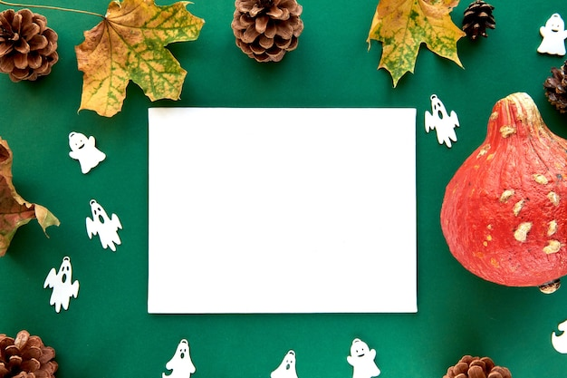 秋の構成。カボチャ、乾燥した葉と装飾的なゴーストの背景。紙の空白のテンプレート秋、秋、ハロウィーン、収穫感謝祭のコンセプト。フラットレイ、上面図、コピースペースの背景