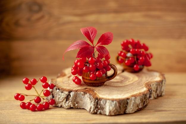 秋の構成。木の鋸で挽かれた木の上の粘土のマグカップの赤いガマズミ属の果実と赤い葉。
