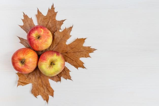 秋の構成熟したリンゴは白い木製の背景に葉を乾燥させます