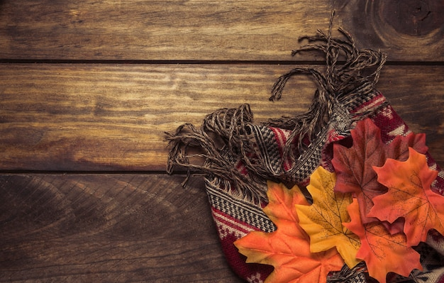 Autumn composition of warm scarf and leaves