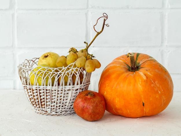 Осенняя композиция с большой тыквой и фруктами. тыква и плетеная корзина с яблоком, грушей и виноградом на белом фоне. свободное место для текста. осенний шоппинг. день благодарения.