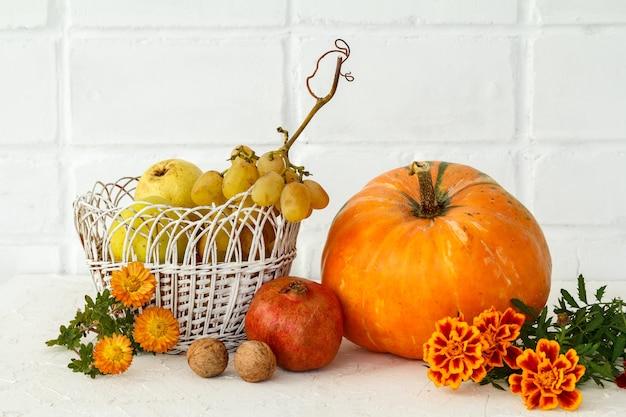 Осенняя композиция с большой тыквой, фруктами и цветами. тыква и плетеная корзина с яблоком, грушей и виноградом на белом фоне. осенний шоппинг. день благодарения.