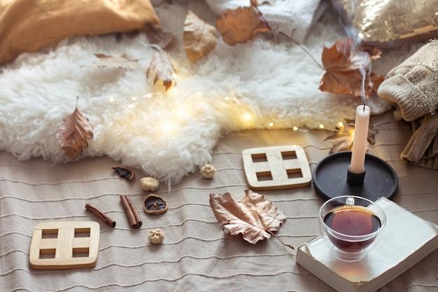 お茶、本、家の装飾の詳細を含む秋の構成。