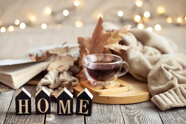 一杯のお茶と装飾品を使った秋の構図。快適さと家庭の居心地のよさの概念。