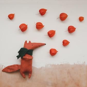 白いテクスチャ背景の上面図におもちゃのキツネとサイサリスの花と秋の構成